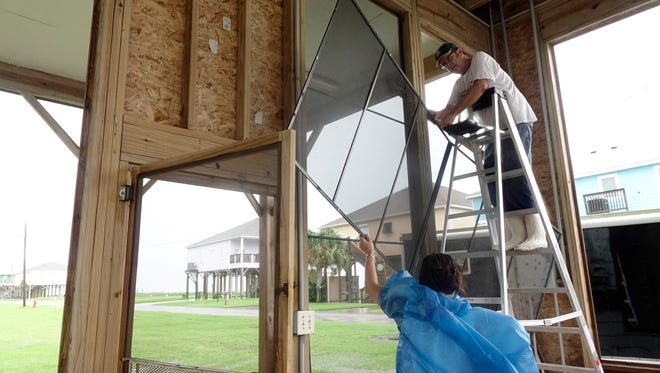 Todd and Debbie Ortego remove screens ferom the camp as early rain squalls from Hurricane Harvey hit Johnson Bayou, La. Friday, August 25, 2017.