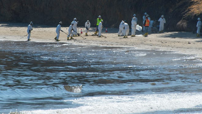 Work crews remove crude oil that washed onto Refugio State Beach after a Plains All American Pipeline pipe broke . The reputure leaked an estimated 21,000 gallons of oil on Santa Barbara County coast.