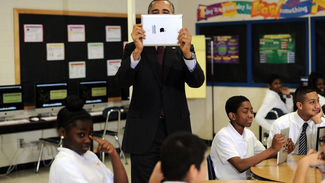 President Obama records video with an iPad as he visits a classroom at Buck Lodge Middle School in Adelphi, Maryland, on February 4, 2014.