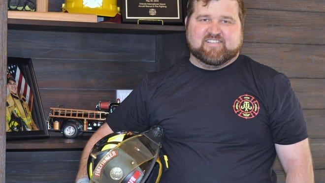 Firefighter Jeremy Saunders stands among his career memorabilia inside his Burlington home. Holding his helmet still gives him goosebumps, he says.