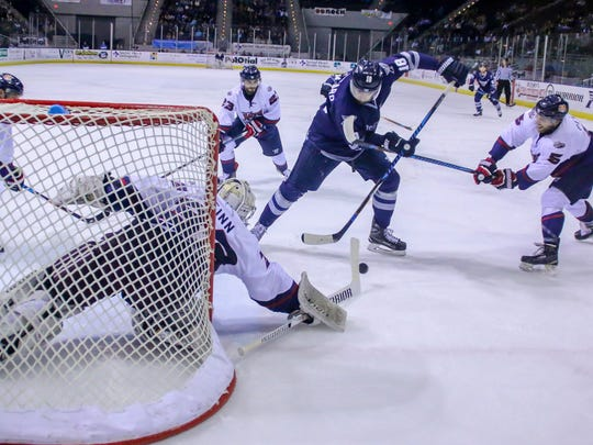 Pensacola's Jessyko Bernard (18) battles past Macon's Brandon Pfeil (5) and tries to get a shot on goal against goaltender Charlie Finn (33) at the Pensacola Bay Center on Sunday, January 14, 2018. Though Macon won the game 4-2, the Ice Flyers have won three of their last five games and stay in first place with 43 points.