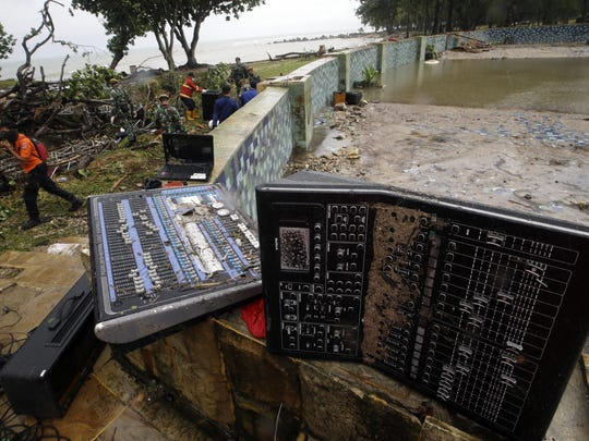 A rescue team walks near an audio mixer damaged by a tsunami at Tanjung Lesung beach resorts Indonesia, Monday, Dec. 24, 2018. The tsunami that roared ashore in Indonesia from the Sunda Strait, killing more than 280 people and injuring over 1,000, was particularly cruel. It hit on a busy holiday weekend when many people were enjoying the warm night breeze on the beach under a full moon. And unlike most big waves, typically alerted by an earthquake's violent shaking, this was a stealth attack. (AP Photo/Achmad Ibrahim)