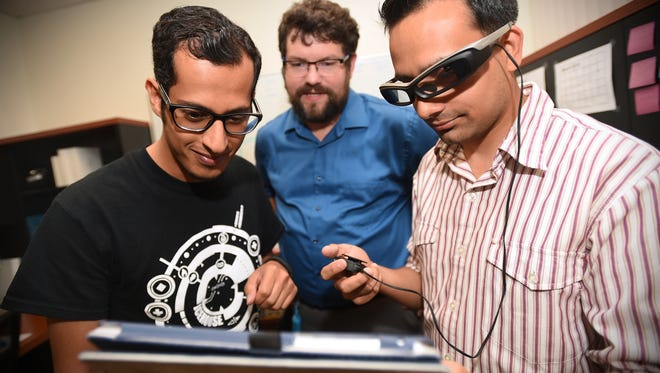 06/23/2016: NMSU computer science graduate students Sultan Alharthi, left, and Hitesh Nidhi Sharma, right, along with computer science professor Zach Toups, demonstrate a wearable disaster response simulation game they developed. The game finished tied for first in the Body Sensor Networks 2016 Icehouse Challenge in San Francisco.