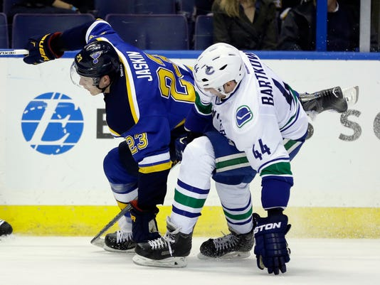 St. Louis Blues' Dmitrij Jaskin, of Russia, and Vancouver Canucks' Matt Bartkowski, right, get tangled up during the second period of an NHL hockey game Friday, March 25, 2016, in St. Louis. (AP Photo/Jeff Roberson)