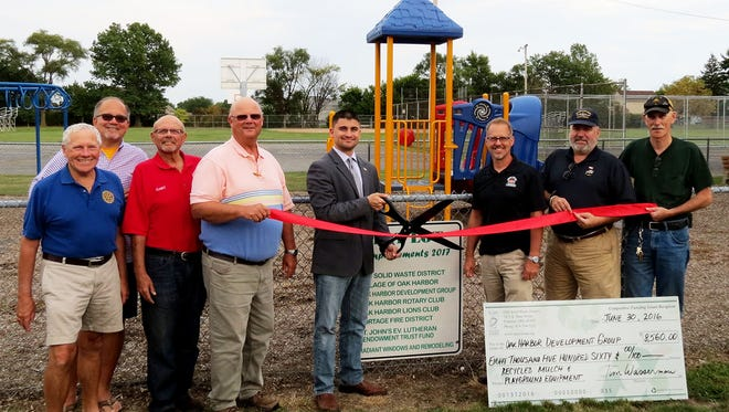 From left: Oak Harbor Lions Club member Clancy DeTray, Ottawa County Commissioner and OSS Solid Waste District board chairman Jim Sass, Mayor of Oak Harbor Joe Helle, Mike Shadoan, of the Oak Harbor Development Group, St. John's Endowment Trust chairman Doug Ceraldi and Kevin Darr, of the Portage Fire District, open the new Tot Lot in Oak Harbor.