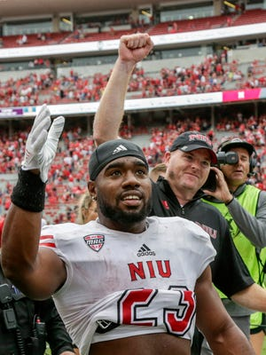 Northern Illinois running back Jordan Huff (front) and head coach Rod Carey celebrate as they walk off the field following a 21-17 win over Nebraska in Lincoln on Saturday.
