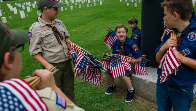 Carson Jakalski, 9, looks up at his fellow Troup members after they finished placing flags at the Nashville National Cemetery in Madison, Tenn., Saturday, May 27, 2017. Groups from across Middle Tennessee gathered to place flags at the National Cemetery in preparation for Memorial Day.