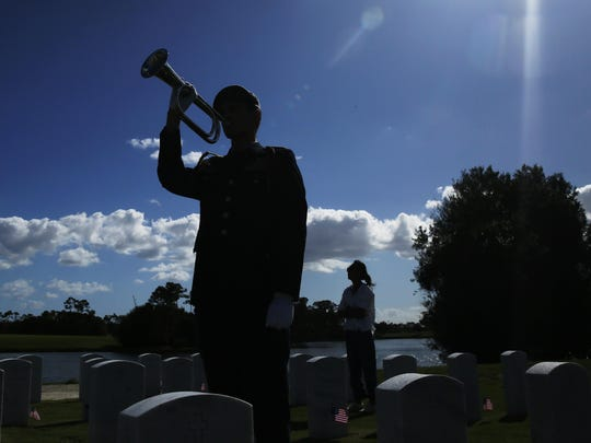 """A member of the military plays """"Taps"""" for a family member during a flag ceremony at the South Florida National Cemetery on Veterans Day on Sunday, Nov. 10, 2019, in Lake Worth, Fla. (AP Photo/Brynn Anderson)"""