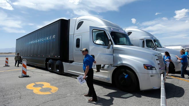 People load in to a Daimler Freightliner Inspiration self-driving truck for a demonstration in May 2015, in Las Vegas. Daimler believes that automated tractor-trailers will be rolling along highways before self-driving cars are cruising around the suburbs.