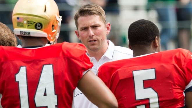 Notre Dame offensive coordinator and quarterbacks coach Mike Sanford (center) brings enthusiasm and inquisitiveness to his new job.