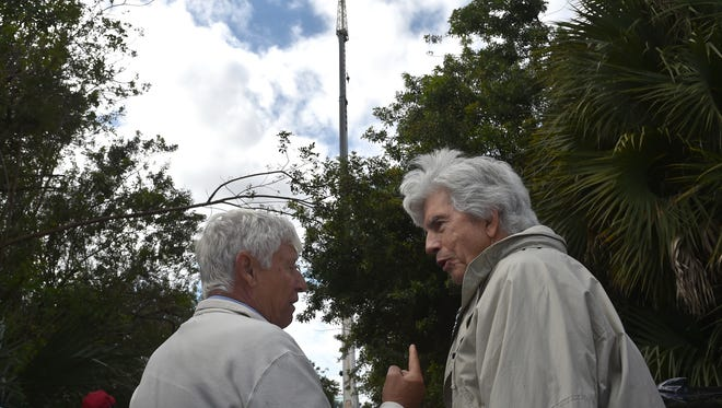 Sandy Kasten (right), a John's Island neighborhood resident, talks with Jerry Weick (left), vice mayor of Indian River Shores, about a proposed cellphone tower in Indian River Shores, a mock version of which is seen in the background in this file photo.