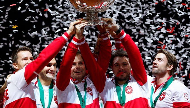 Swiss Davis Cup team players celebrate with the trophy after defeating France in the Davis Cup World Final at the Pierre Mauroy Stadium in Lille, France.