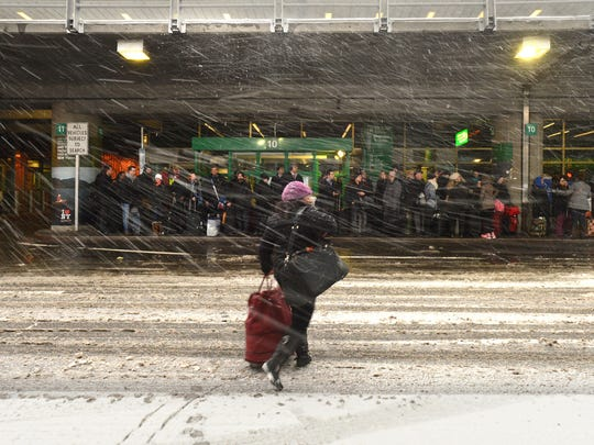 People are seen at LaGuardia Airport in Queens, N.Y., as a significant blizzard that is predicted to strike a wide swath of the East Coast has already begun disrupting air travel.