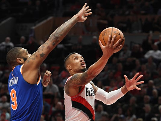 Portland Trail Blazers guard Damian Lillard drives to the basket on New York Knicks center Kyle O'Quinn during the second half of an NBA basketball game in Portland, Ore., Tuesday, March 6, 2018. Lillard scored 37 points as the Blazers won 111-87.(AP Photo/Steve Dykes)