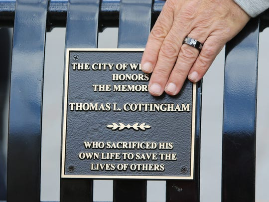 "Friends and family of Thomas L. ""Cannibal"" Cottingham help dedicate a bench in his name at Rodney Square in Wilmington."