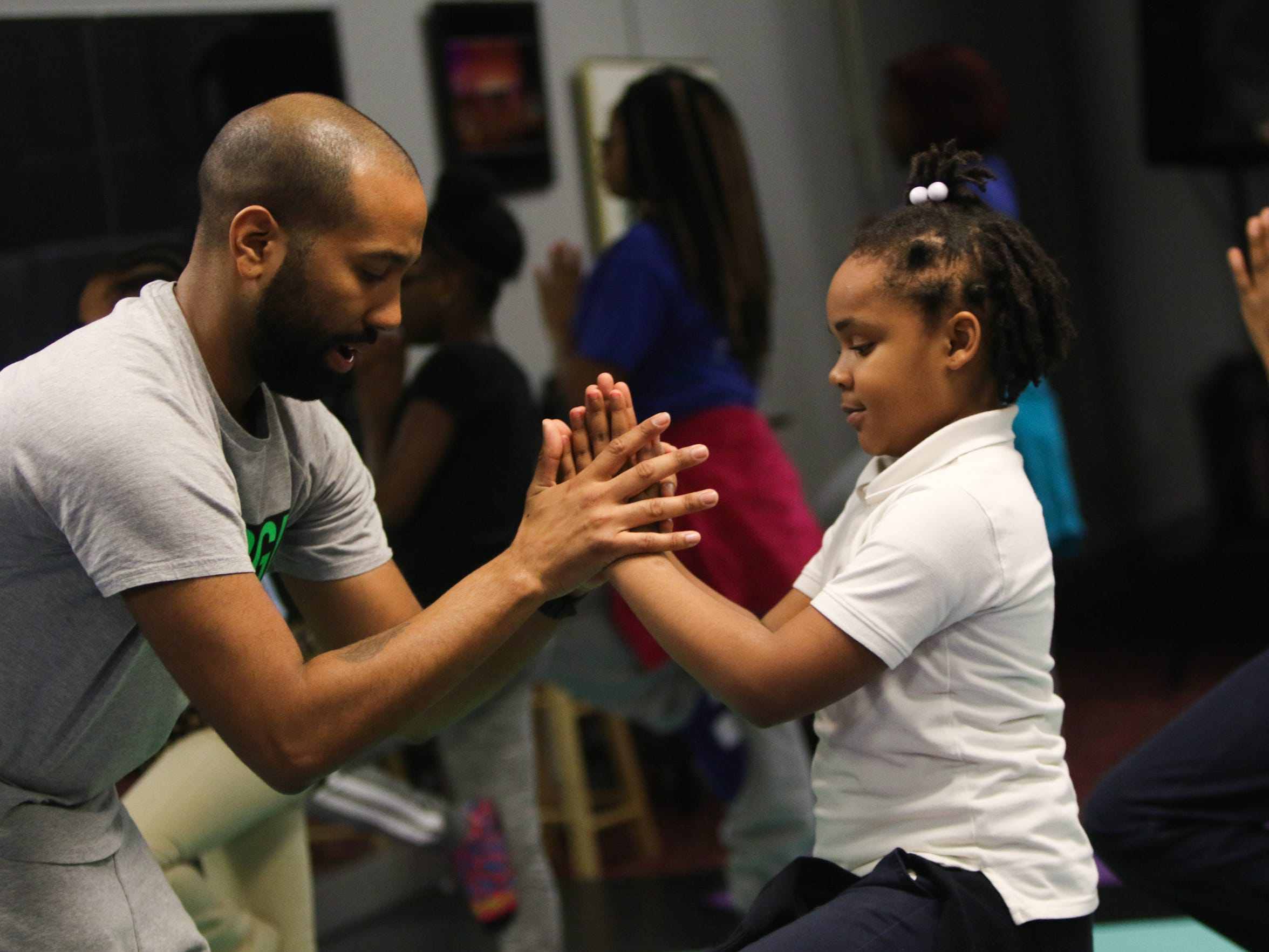 Yoga instructor Jason Aviles helps steady NyAsiah Coleman as she attempts a tree pose during yoga class at Christina Cultural Art Center's HeArt Under the Hoodie Youth Violence Prevention Program Thursday.