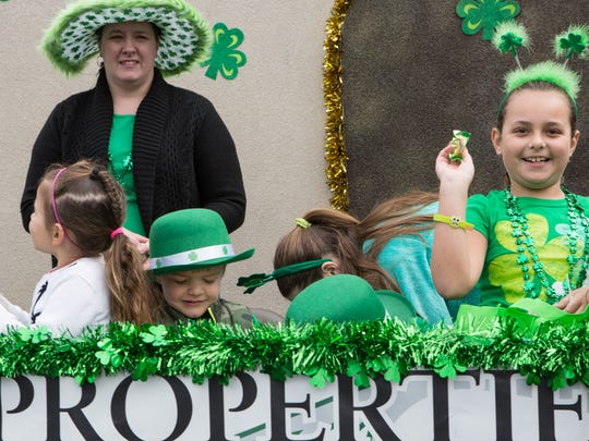 Children throw candy to a crowd on a parade float on Coastal Highway in Ocean City during the Saint Patrick's Day parade on Saturday, March 12, 2016.