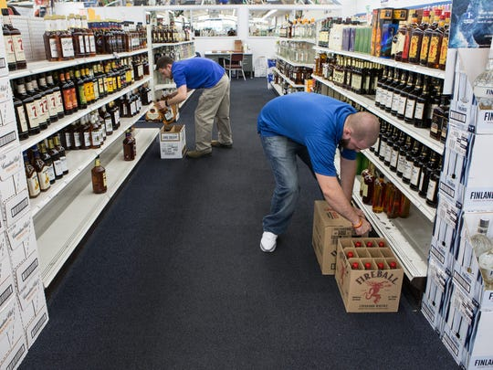 Brooks Handy, left, of Salisbury, and Michael Cooper, of Salisbury, restocks bottles of liquor at the Wicomico County Liquor Dispensary on South Salisbury Boulevard on Tuesday, March 29, 2016.