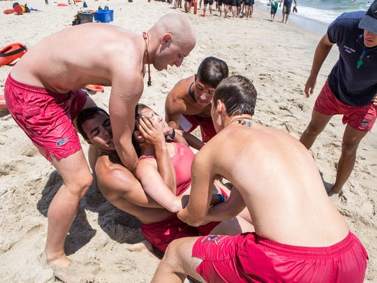 Members of the Ocean City Beach Patrol practice a life-saving procedure on a fellow lifeguard during a re-certification session. The procedure, called the Hawaiian Sling, is a rescue technique in which lifeguards operate as a human backboard.