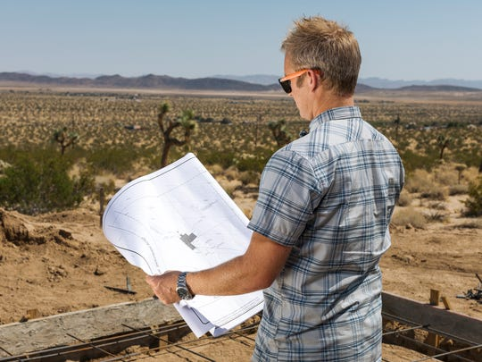 Troy Kudlac looks over plans for Joshua Tree Modern, four 1,300-square-foot houses on 10 acres in south Joshua Tree.