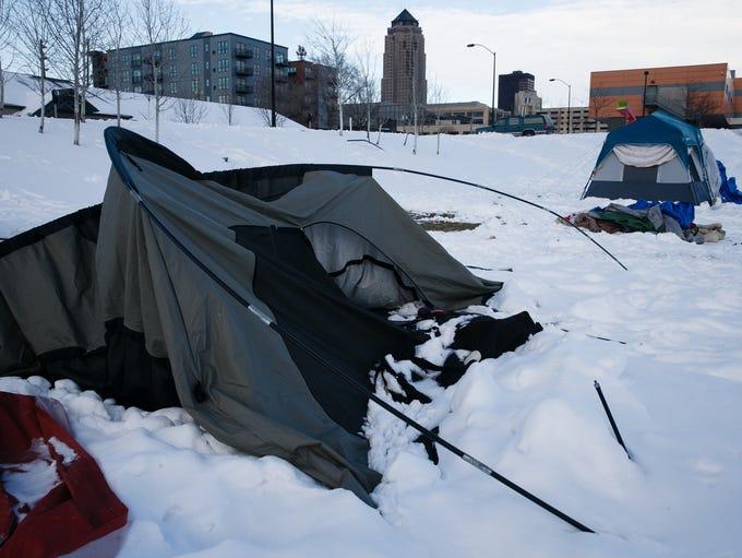 A homeless encampment sits along the railroad tracks