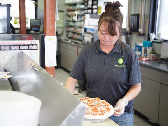 Joey Lewis of Wever makes a pizza at the Wever Junction gas station on Tuesday, March 20, 2018, in Wever. The station saw a huge influx of customers during construction of the nearby fertilizer plant last year and was able to make improvements and bring on more staff, like Lewis, with the extra funds.