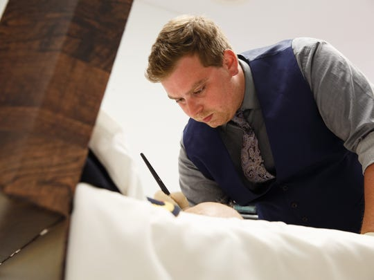 Lance Angstman knew he wanted to be a funeral director since he was 11 years old. At 17 he got his first job at a funeral home and, at 27, he is a funeral director at Mitchell Family Funeral Home. Here he applies makeup to a client on Tuesday, May 15, 2018, in Marshalltown.