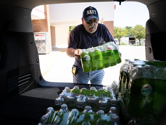Fred Franklin of Creston loads cases of water into