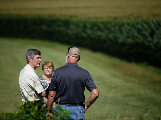 Iowa governor candidate Fred Hubbell, center, is shown around the Jasper County farm of Mark Tinnermeier, right, and his wife, Pat, center, during a July 11 campaign stop near Newton.
