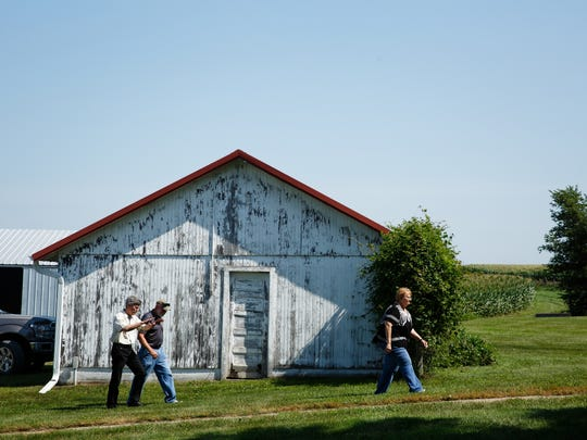 Iowa governor candidate Fred Hubbell, left, walks to the home of Mark Tinnermeier, center, and his wife, Pat, right, after touring their Jasper County farm during a July 11 campaign stop.