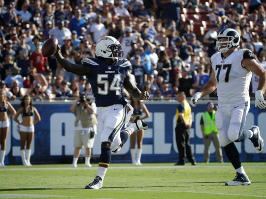 Chargers defensive end Melvin Ingram just beats Rams offensive tackle Andrew Whitworth to the end zone after recovering a fumble and running 76 yards for a touchdown during Saturday's preseason game.