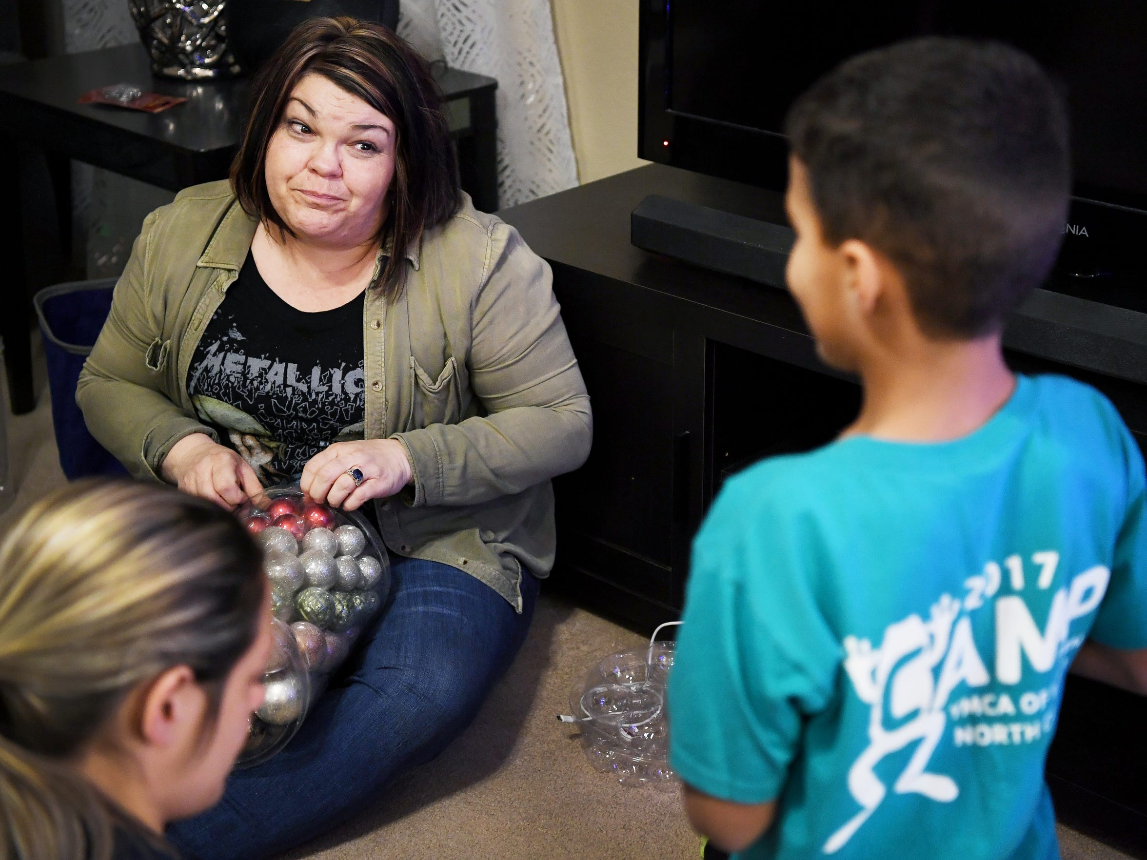 Shantel Wyatt talks to Emanie, a foster child in her care, as they decorate their Christmas tree November 30, 2017.