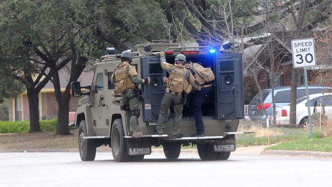 Members of SWAT deploy at a house in the 2500th block of Elmwood Drive, just across from Austin Elementary School, urging the resident inside to talk to them, or open the door.