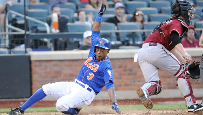 New York Mets' Curtis Granderson scores on a double by Bobby Abreu as Diamondbacks catcher Tuffy Gosewisch, right, takes the throw during the fifth inning of the second game of a baseball double-header Sunday, May 25, 2014, at Citi Field in New York.