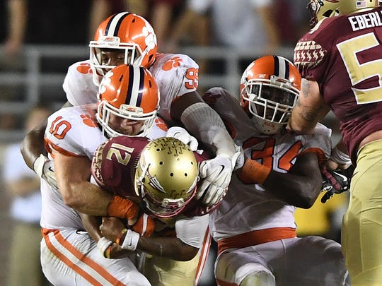 Clemson linebacker Ben Boulware (10), defensive lineman Clelin Ferrell (99), and linebacker Kendall Joseph (34) sack Florida State quarterback Deondre Francois (12) during the 4th quarter at Florida State's Doak Campbell Stadium in Tallahassee, Fl. on Saturday, October 29, 2016.