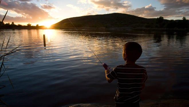 Gabriel Arellano, 11, of Tucson, fishes during twilight at Patagonia Lake State park in Patagonia, AZ.