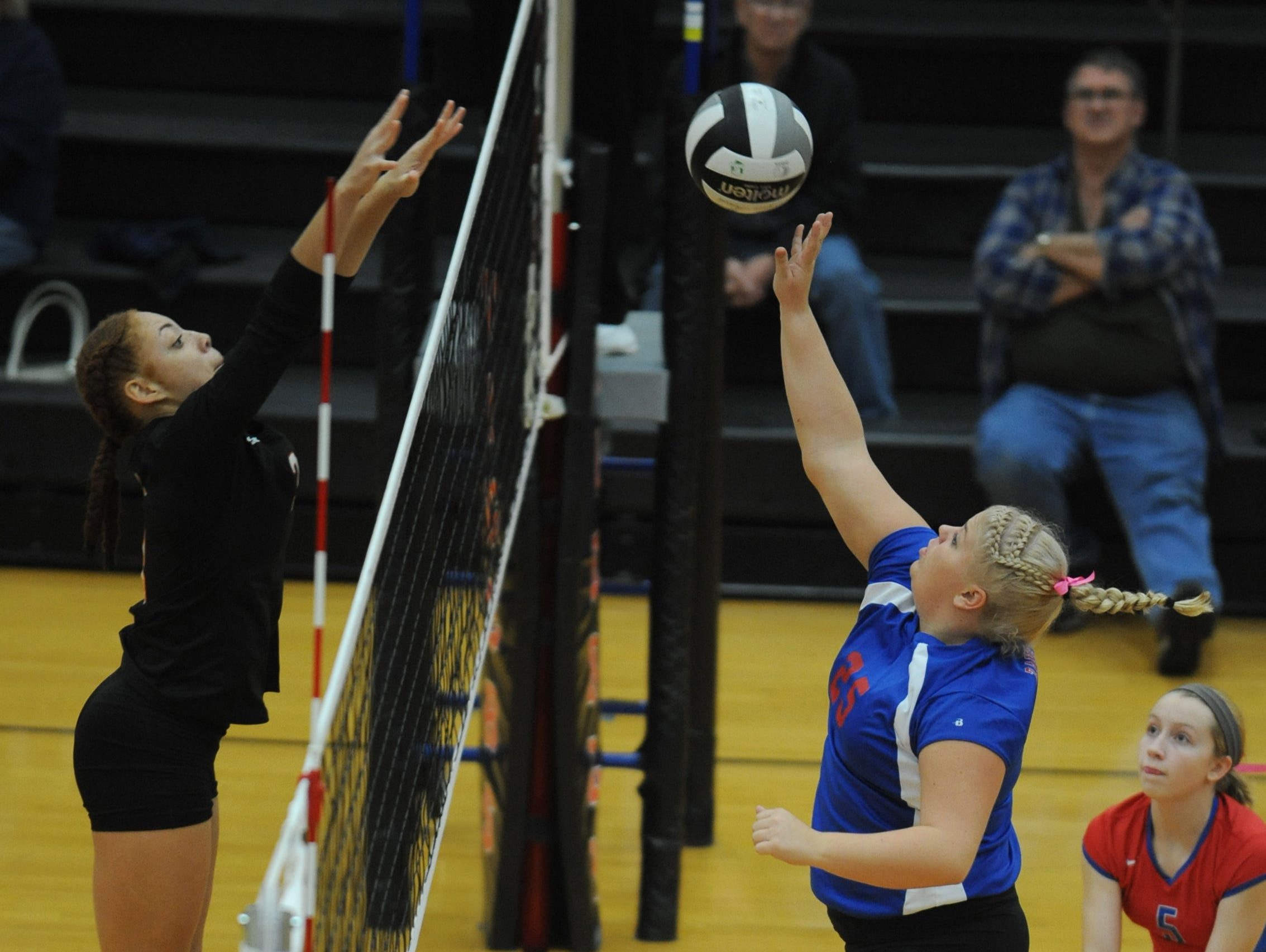 Zane Trace's Kelly Dresbach tips the ball over an Ironton opponent Wednesday at Waverly High School. Zane Trace defeated Ironton 3-1.
