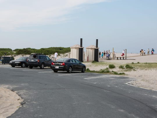 Beachgoers travel to and from the South Ocean Beach parking lot at Assateague Island National Seashore on Tuesday, June 30.