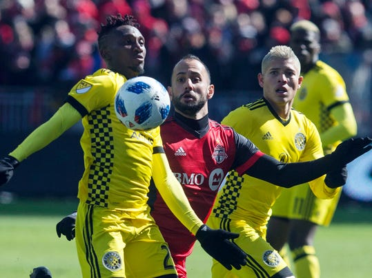 Columbus Crew defender Harrison Afful, left, chests the ball away from Toronto FC midfielder Victor Vazquez, center, during the first half of an MLS soccer game in Toronto on Saturday, March 3, 2018. (Chris Young/The Canadian Press via AP)