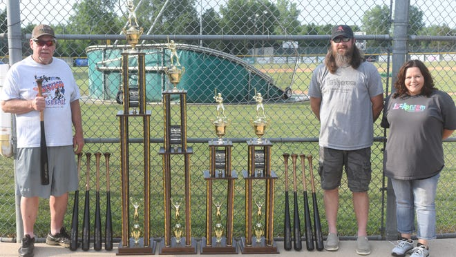 Lockeroom head coach Lester White (from left), Lockeroom owner Jason Wingate and store manager Donna Kelso display the team trophies and bats that will be given for individual awards at this week's Mickey Huskey Lockeroom Twin Lakes Classic. The American Legion Baseball tournament will be held Thursday through Sunday at Cooper Park.
