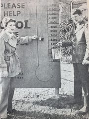 Contributions from local citizens in January 1980 had raised just over $9,000 for Morganfield Elementary's Cool the School fundraiser. Alice B. Huelette and Buddy Whitledge are shown painting the school's campaign board to reflect the new total. Huelette designed the sign and Whitledge represented the Morganfield Jaycees who had raised $380 with a bucket brigade for the cause. The total goal for the fundraiser was $12,000.