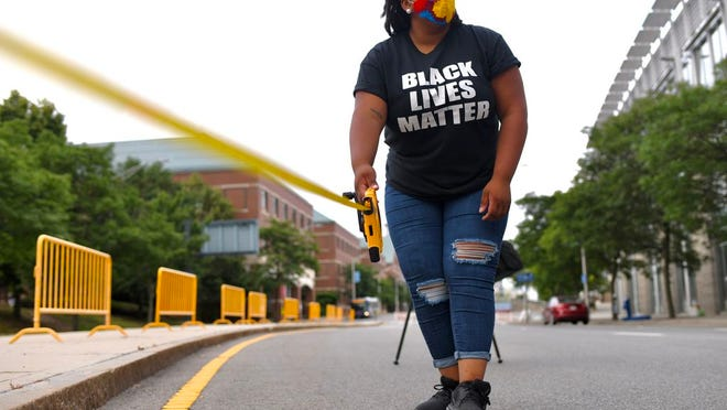 Casey Thomas of Worcester measures the road for Black Lives Matter letters on Wednesday morning.