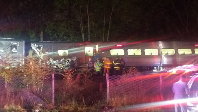 Rescue personnel look at a Long Island Railroad train that derailed near New Hyde Park, N.Y., Saturday, Oct. 8, 2016.  The commuter train derailed after it hit a work train on the tracks.