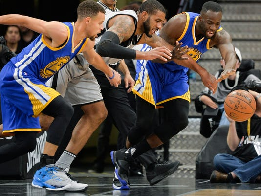 San Antonio Spurs forward LaMarcus Aldridge, center, chases the ball against Golden State Warriors' Stephen Curry (30) and Draymond Green during the first half of an NBA basketball game, Saturday, March 19, 2016, in San Antonio. (AP Photo/Darren Abate)