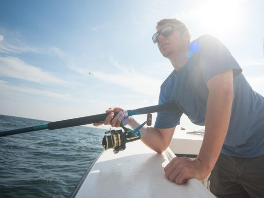 Ryan Marshall begins to reel in a croaker during a fishing trip off the coast of Bethany Beach.