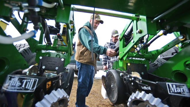 Frank Schroeder, left, and David Schroeder, both from Cecil, look over a planter on display during the 2013 WPS Farm Show at the EAA grounds in Oshkosh.