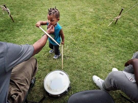 One-year-old Jaden Mujahid tries to fend off his grandfather's smudge cleaning efforts as Michael Turner and other members of the Greater Faith Church of God in Christ choir and praise band prepare to perform in Robert R. Church Park Sunday during the final day of the Memphis Juneteenth Urban Music Festival.
