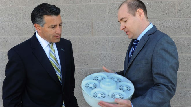 Nevada Gov. Brian Sandoval, left, listens as Ashima Devices President and CEO Mark Richardson explains his company's drone product, which will be manufactured in Stead.
