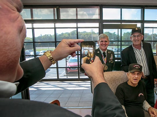 Mike Firetti, son-in-law of U.S. Army veteran John Dorval Minatra, seated, takes a photo of Minatra along with U.S. Army Sgt. Major Mike Hall and Army Maj. Mike Wager, both retired, at the close of a ceremony honoring Minatra for his military service.