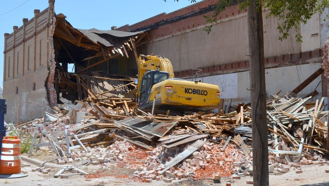 Heavy equipment rips through the old Bowden's Department Store Friday morning in Vernon at the corner of Main and Olive streets. The city received a grant from NORTEX Regional Planning Commission to demolish a city-owned building. Linda Stewart/Special to the Times Record News